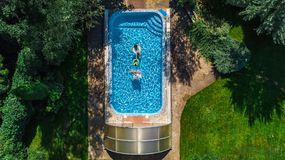 Aerial top view of family in swimming pool from above, mother and kids swim on inflatable ring donuts and have fun in water. Aerial top view of family in Royalty Free Stock Photography