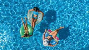 Aerial top view of family in swimming pool from above, mother and kids swim on inflatable ring donuts and have fun in water. Aerial top view of family in Stock Images
