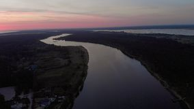 Aerial top view fly over river Lielupe in Jurmala, Latvia Spring 2019 during sunrise with crimson violet and pink sky - stock video