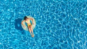 Aerial top view of girl in swimming pool from above, kid swims on inflatable ring donut , child has fun in water on vacation. Aerial top view of girl in swimming Royalty Free Stock Photography
