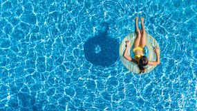 Aerial top view of girl in swimming pool from above, kid swims on inflatable ring donut , child has fun in water on vacation. Aerial top view of girl in swimming Royalty Free Stock Images