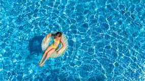 Aerial top view of girl in swimming pool from above, kid swims on inflatable ring donut , child has fun in water on vacation. Aerial top view of girl in swimming Stock Image