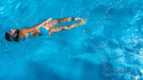 Aerial top view of girl in swimming pool water from above, tropical vacation holiday Stock Images
