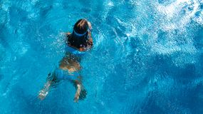 Aerial top view of girl in swimming pool water from above, tropical vacation holiday Royalty Free Stock Photo
