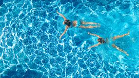 Aerial top view of girls in swimming pool water from above, active children swim, kids have fun on tropical family vacation. Holiday resort concept stock images