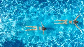 Aerial top view of girls in swimming pool water from above, active children swim, kids have fun on tropical family vacation. Holiday resort concept royalty free stock photos