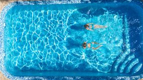 Aerial top view of girls in swimming pool water from above, active children swim, kids have fun on tropical family vacation. Holiday resort concept royalty free stock photography