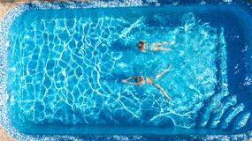 Aerial top view of girls in swimming pool water from above, active children swim, kids have fun on tropical family vacation. Holiday resort concept royalty free stock images