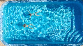 Aerial top view of girls in swimming pool water from above, active children swim, kids have fun on tropical family vacation. Holiday resort concept royalty free stock photo