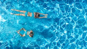 Aerial top view of girls in swimming pool water from above, active children swim, kids have fun on tropical family vacation. Holiday resort concept stock photography