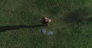 Aerial view of woman standing on the grass while drone is taking off the sunglasses from her face. Aerial top view of happy woman standing on the grass during stock footage