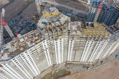 Aerial top view of high-rise residential buildings under construction and cranes stock images