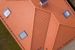 Aerial top view of house metal shingle roof, brick chimneys and small plastic attic windows. Roofing, repair and renovation work.  royalty free stock photos