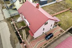Aerial top view of house with shingle roof and brick chimney in quiet neighborhood, black car on paved yard. Well maintained. Property concept stock images