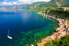 Aerial top view of small fishing village Chianalea di Scilla, It. Aerial top view of houses and white yacht ship in small fishing village Chianalea di Scilla stock photography