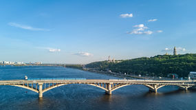 Aerial top view of Metro railway bridge with train and Dnieper river from above, skyline of city of Kiev. Ukraine Royalty Free Stock Photos
