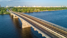 Aerial top view of Metro railway bridge with train and Dnieper river from above, skyline of city of Kiev. Ukraine Royalty Free Stock Photo