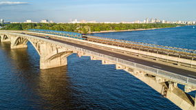 Aerial top view of Metro railway bridge with train and Dnieper river from above, skyline of city of Kiev. Ukraine Stock Image
