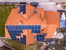 Aerial top view of new modern residential house cottage with blue shiny solar photo voltaic panels system on roof. Renewable. Ecological green energy production royalty free stock photo