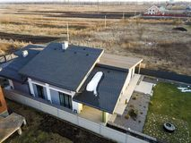 Aerial top view of new residential house cottage and terrace with shingle roof on fenced big yard on sunny winter day.  royalty free stock photos