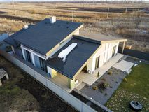 Aerial top view of new residential house cottage and terrace with shingle roof on fenced big yard on sunny winter day.  stock images