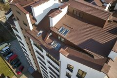Aerial top view of new tall apartment building with annex room covered with metal siding and attic windows in quiet area.  stock image