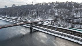 Aerial top view of pedestrian Park bridge in winter and Dnieper river from above, snow Kyiv cityscape, city of Kiev skyline Royalty Free Stock Photo