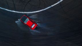 Aerial top view professional driver drifting car on wet race track, with water splash, red car. royalty free stock images