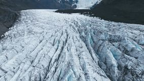 Aerial top view of the ridges of white glacier with black ash and a lake stock video footage