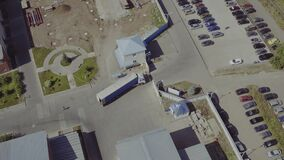 Aerial top view of ruck with Attached Semi Trailer Leaving Industrial Plant, Storage Building, Loading Area. Aerial view