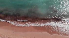 Aerial top view of sandy beach. Blue crystal clear water. Drone flies through beautiful beach. Ocean waves creating foam. Drone to stock video