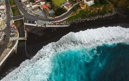 Aerial top view of sea waves hitting a beach with black volcanic sand with turquoise sea water. Seascape in the Portuguese coastline. Azores islands. Drone royalty free stock photo