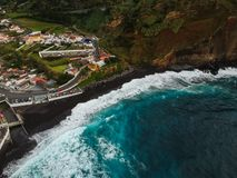 Aerial top view of sea waves hitting a beach with black volcanic sand with turquoise sea water. Seascape in the Portuguese coastline. Azores islands. Drone stock image