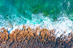 Aerial top view of sea waves hitting rocks on the beach.  royalty free stock photography