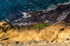 Aerial top view of sea waves hitting rocks on the shore with turquoise sea water royalty free stock images