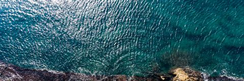 Aerial top view of sea waves hitting rocks on the shore with turquoise sea water royalty free stock photo