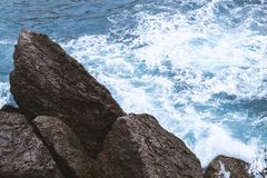 Aerial top view of sea waves hitting rocks stock photos