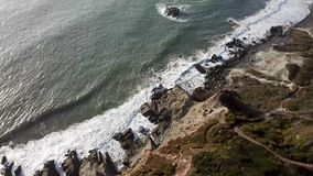 Aerial top view of sea waves hitting rocky shore stock video
