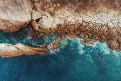 Aerial top view of sea waves and stone rocky beach coast, drone photo.  royalty free stock photos