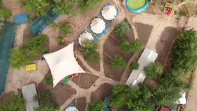 Aerial top view shot of the luxury camping with big white tents and marquees, Stylized territory, trails and camp