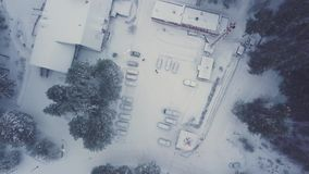 Aerial top view of snow covered house, parked cars and green pine trees in winter time. Clip. Empty yard in frosty stock video footage