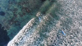 Aerial top of view of surfers on the ocean at sunset and wave. Stock Image