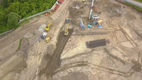 Aerial top view of three tip trucks standing next to each other awaiting loading of sand and soil on a construction site and a cou