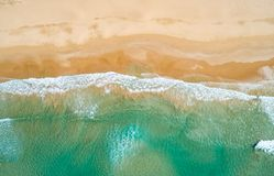 Aerial view to tropical sandy beach and blue ocean. Top view of ocean waves reaching shore on sunny day. Palawan, Philippines. Aerial top view of turquoise ocean stock images