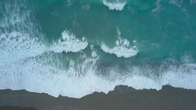 Aerial top view turquoise sea waves from bird`s eye view, ocean waves reaching shore and splashing. Aerial top view turquoise sea waves break on empty sand beach stock video