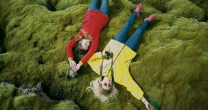 Aerial top view of the two happy woman lying on the soft moss in lava field in Iceland. Tourists resting on nature. stock footage