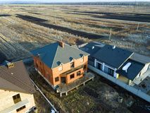 Aerial top view of two new residential houses cottages with shingle roof on fenced big yards on sunny day.  royalty free stock photo