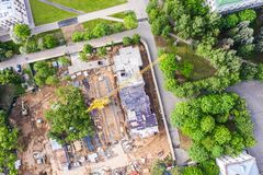 Aerial top view of urban area construction site with high yellow tower crane royalty free stock photos