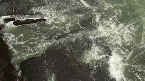 Aerial top view waves break on dark rocks near beach. Sea waves ocean waves on the rock view on beautiful beach. Aerial top view waves break on dark rocks near stock footage