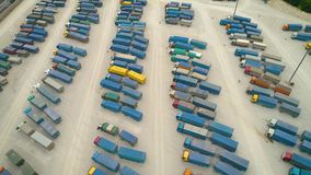 Aerial Top View of White Semi Truck with Cargo Trailer Parking with Other Trucks on Special Parking Lot. Shot on Phantom